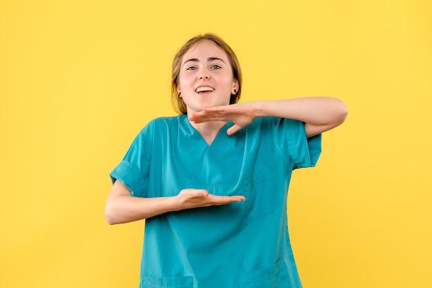 Vorderansicht ärztin, die auf gelbem hintergrundkrankenhausgesundheits-emotionsmediziner aufgeregt fühlt