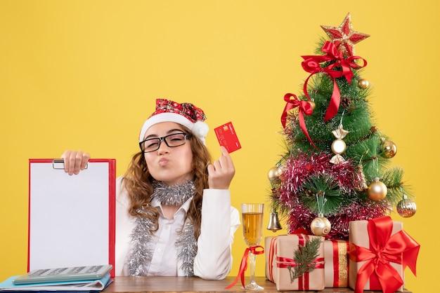 Vorderansicht ärztin, die bankkarte und aktenschein hält