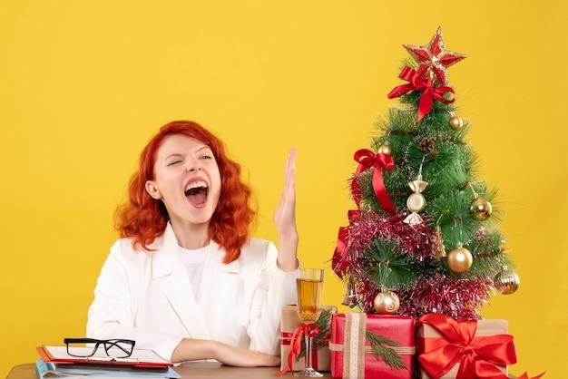 Vorderansicht-ärztin, die hinter tisch mit weihnachtsgeschenken sitzt und ihre hand auf gelbem hintergrund erhebt