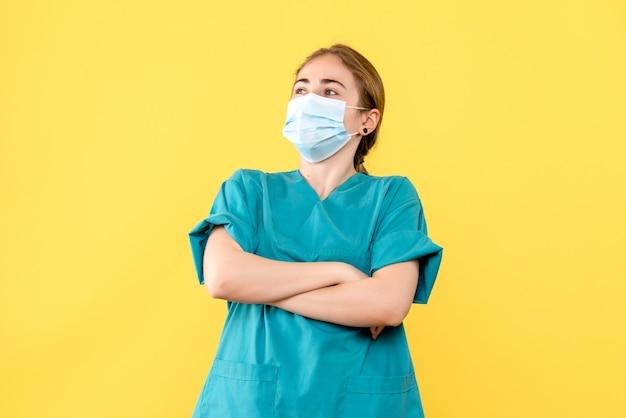Vorderansicht ärztin, die in der maske auf gelbem hintergrundvirus-gesundheitspandemie-covid- posiert
