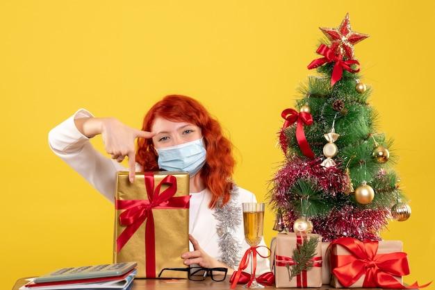 Vorderansicht ärztin, die in maske mit weihnachtsgeschenken und baum auf gelbem hintergrund mit weihnachtsbaum und geschenkboxen sitzt
