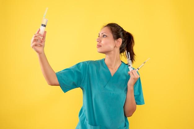 Vorderansicht ärztin, die injektionen auf gelbe schreibtischkrankenhauskrankheit farbmedizinervirus-krankenschwestergesundheit hält