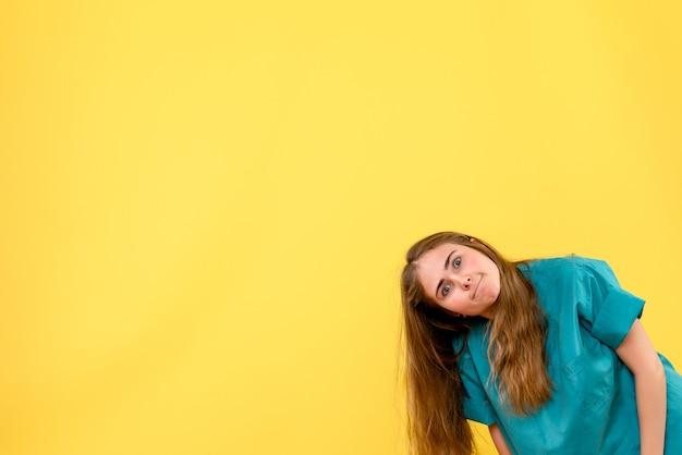 Vorderansicht-ärztin, die lustiges gesicht auf gelbem hintergrundgesundheitsmediziner-krankenhausemotion macht