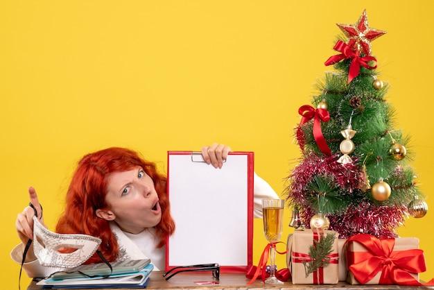 Vorderansicht-ärztin, die maske und aktennotiz um weihnachtsbaum hält