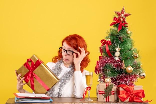 Vorderansicht-ärztin, die mit weihnachtsgeschenken und baum auf gelbem hintergrund sitzt