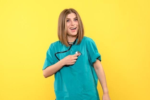 Vorderansicht-ärztin, die tonometer auf gelbem raum hält