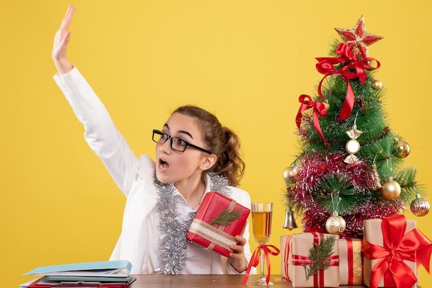 Vorderansicht ärztin, die weihnachtsgeschenk hält