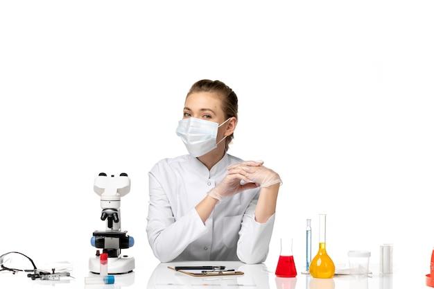 Vorderansicht ärztin im medizinischen anzug, der maske wegen covid auf leerraum trägt