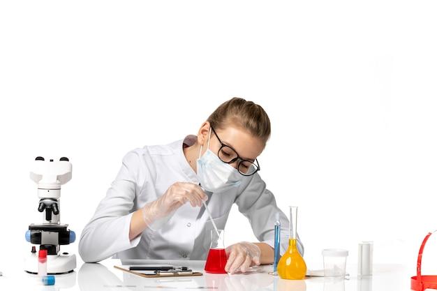 Vorderansicht ärztin im medizinischen anzug, die maske wegen der koviden arbeit mit lösungen auf leerraum trägt