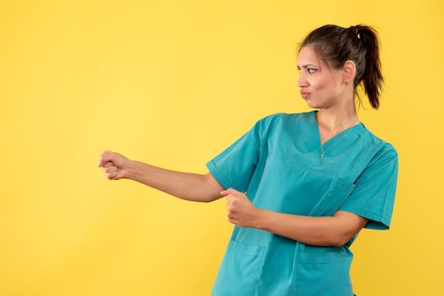 Vorderansicht ärztin im medizinischen hemd auf gelbem schreibtischkrankenschwester-gesundheitskrankenhaus-krankenhaus-covid-virus