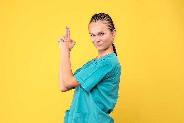 Vorderansicht ärztin im medizinischen hemd, covid-19 gesundheitskrankenhausvirus-farbemotion