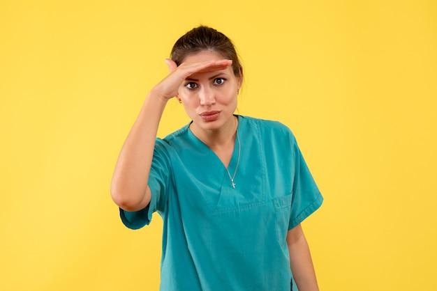 Vorderansicht ärztin im medizinischen hemd, das auf gelbem hintergrund schaut