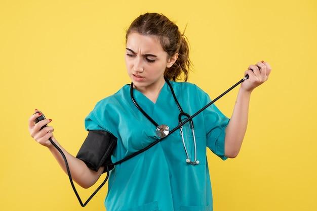 Vorderansicht ärztin im medizinischen hemd, die ihren druck prüft, virusgesundheits-emotion uniform covid-19-pandemie