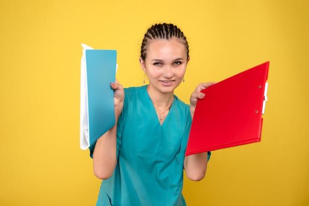 Vorderansicht ärztin im medizinischen hemd mit notizen, farbe gesundheit krankenschwester covid-19 emotionsmediziner
