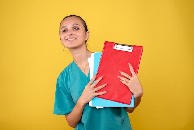 Vorderansicht ärztin im medizinischen hemd mit notizen, krankenhausfarbe gesundheit covid-19 emotionsmediziner