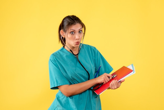 Vorderansicht ärztin im medizinischen hemd mit stethoskop und notizen auf gelbem hintergrund
