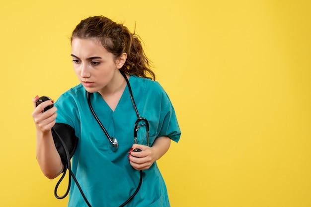 Vorderansicht ärztin im medizinischen hemd prüft ihren druck, virusgesundheit emotion uniform covid-