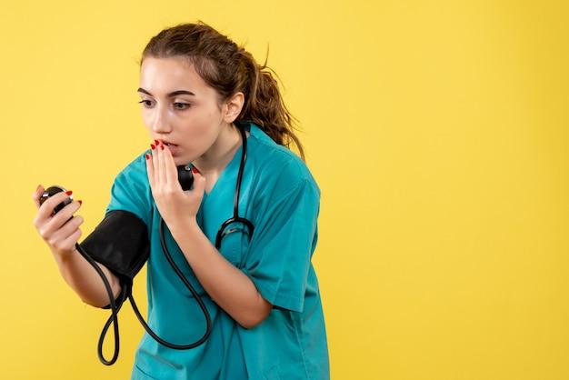 Vorderansicht ärztin im medizinischen hemd prüft ihren druck, virusgesundheitsgefühle einheitliche covid-19-pandemie