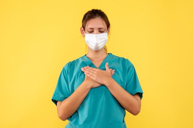 Vorderansicht-ärztin im medizinischen hemd und in der maske auf gelbem hintergrund Kostenlose Fotos