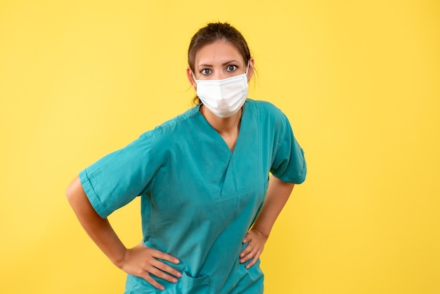 Vorderansicht-ärztin im medizinischen hemd und in der maske auf gelbem hintergrund