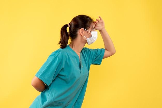 Vorderansicht-ärztin im medizinischen hemd und in der sterilen maske auf gelbem hintergrund