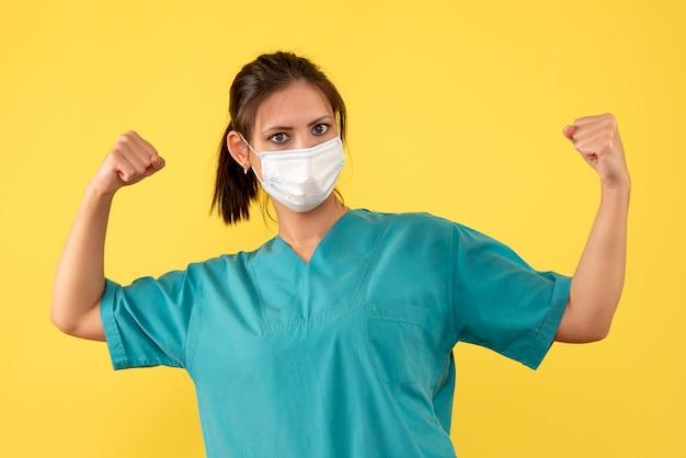 Vorderansicht ärztin im medizinischen hemd und mit steriler maske auf gelbem hintergrund