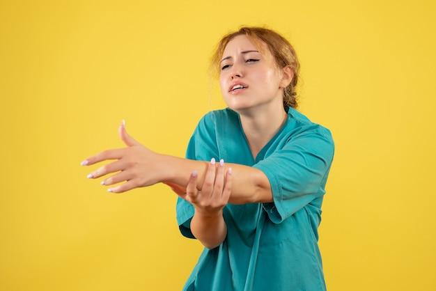 Vorderansicht ärztin im medizinischen hemd verletzte ihre hand, sanitäter covid-19 krankenschwester farbe gesundheit