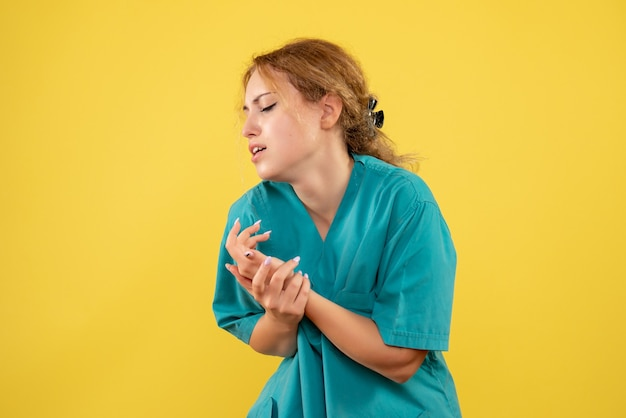 Vorderansicht ärztin im medizinischen hemd verletzte ihren arm, sanitäter covid-19 krankenschwester farbe gesundheit