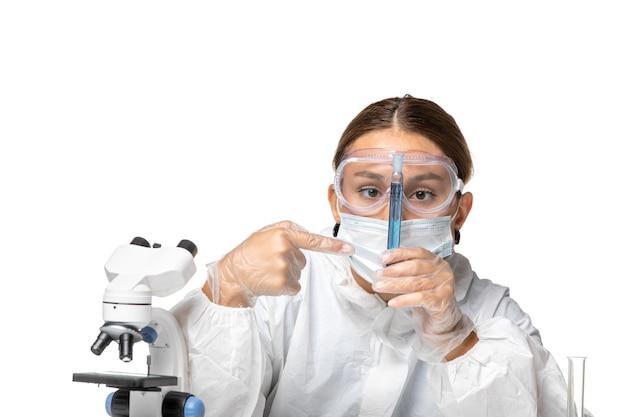Vorderansicht ärztin im schutzanzug und mit maskenhaltekolben mit blauer lösung auf hellweißem hintergrund covid virus pandemie coronavirus