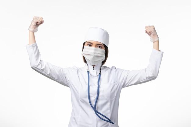 Vorderansicht ärztin im weißen medizinischen anzug mit einer maske aufgrund des coronavirus, das auf der weißen wandgesundheitskrankheit pandemische covid- biegt.