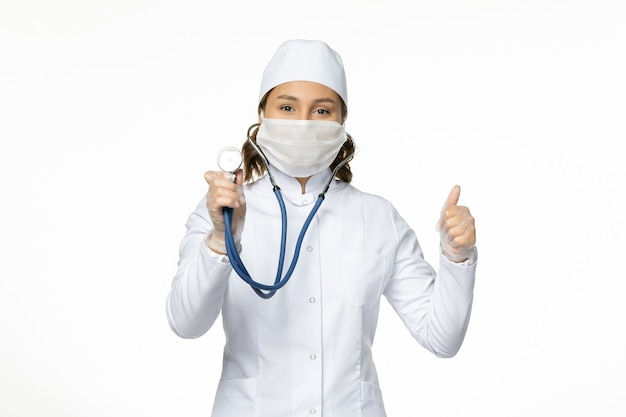 Vorderansicht ärztin im weißen medizinischen anzug und in der maske unter verwendung des stethoskops auf der weißen wandpandemievirus-krankheitsmedizin