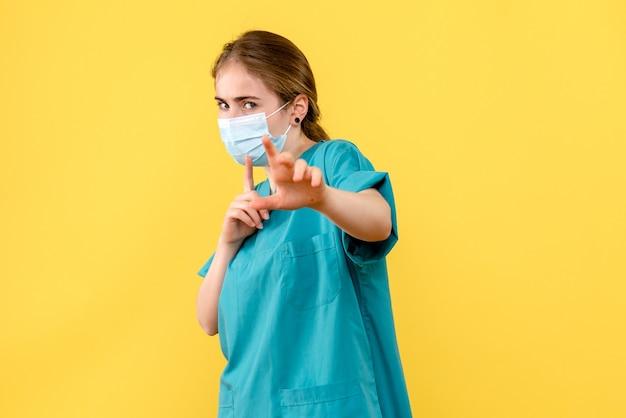 Vorderansicht ärztin in maske auf gelbem hintergrund gesundheitskrankenhaus covid pandemie