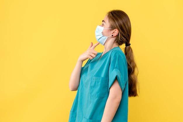 Vorderansicht ärztin in maske auf gelbem hintergrund gesundheitskrankenhaus pandemie covid