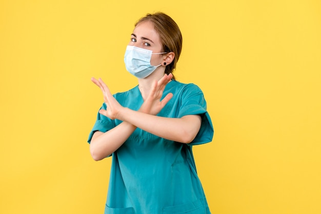 Vorderansicht ärztin in maske auf gelbem schreibtisch gesundheitskrankenhaus covid pandemie