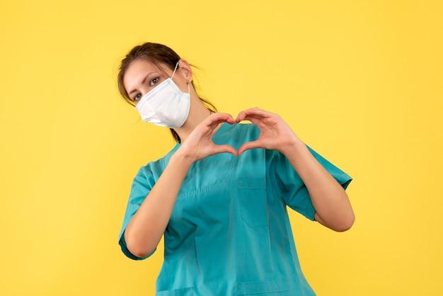 Vorderansicht ärztin in medizinischem hemd und maske auf gelbem schreibtischmediziner-pandemie-covid-krankenhausfarbvirusgesundheit
