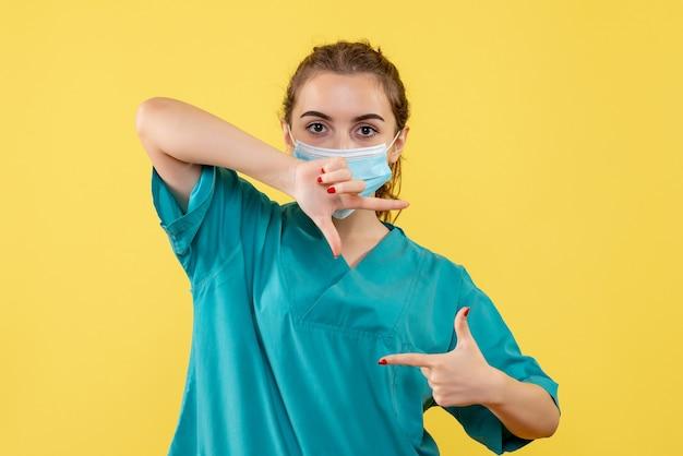 Vorderansicht ärztin in medizinischem hemd und maske, einheitliche virusgesundheitsfarbe covid pandemie
