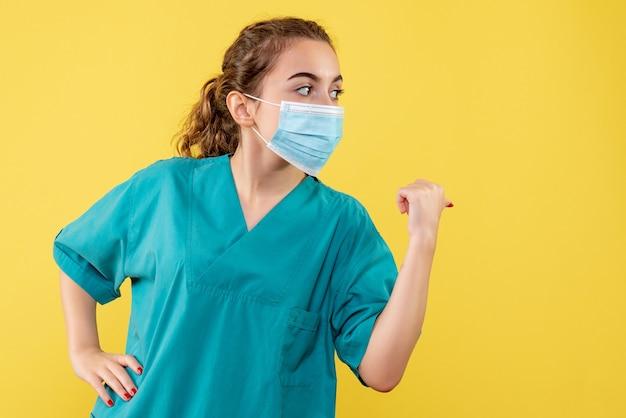 Vorderansicht ärztin in medizinischem hemd und maske, farbe pandemie-gesundheitsvirus covid-19 uniform