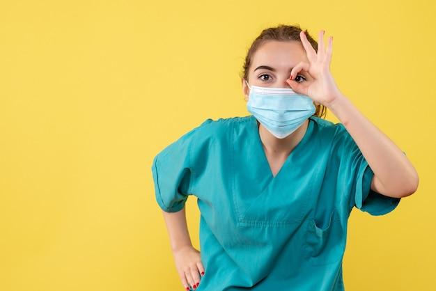 Vorderansicht ärztin in medizinischem hemd und maske, farbe pandemievirus covid-19 uniform