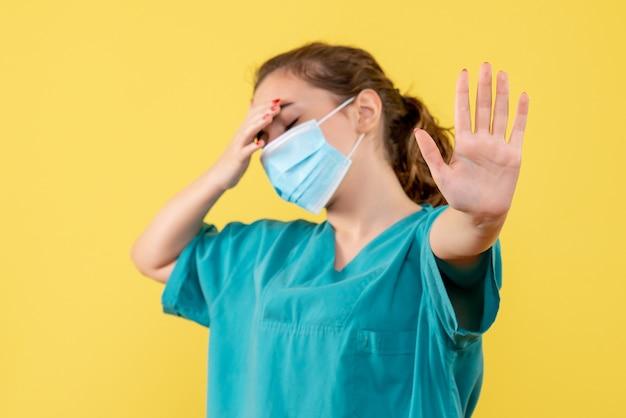 Vorderansicht ärztin in medizinischem hemd und maske gestresst, gesundheitsfarbe pandemievirus covid-19 uniform coronavirus