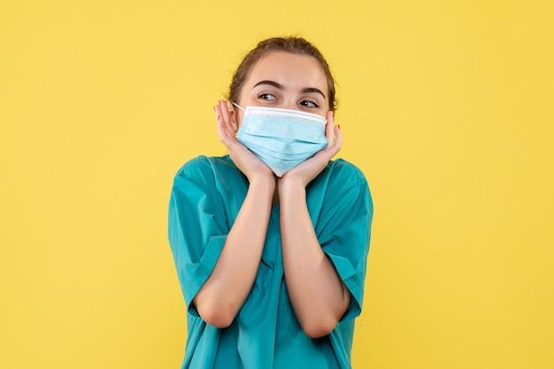Vorderansicht ärztin in medizinischem hemd und maske, gesundheitsuniformvirus covid-19-pandemiefarbe