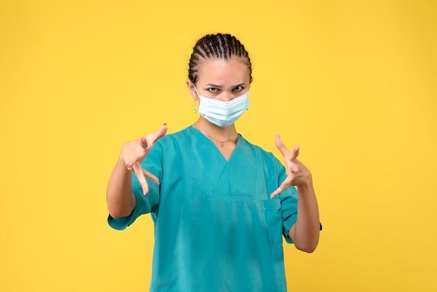 Vorderansicht ärztin in medizinischem hemd und maske, krankenpflegerkrankenhausvirus covid-19-pandemiefarbe