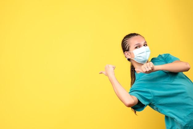 Vorderansicht ärztin in medizinischem hemd und maske, pandemievirus-gesundheitskrankenhaus covid farbkrankenschwester