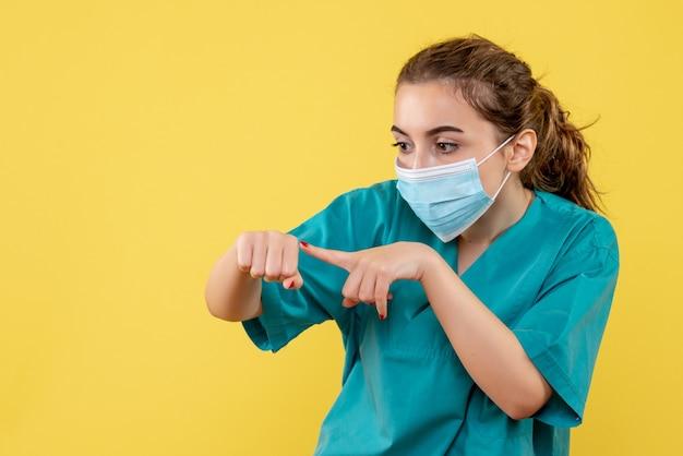 Vorderansicht ärztin in medizinischem hemd und maske, viruspandemie einheitliche farbe covid-19 coronavirus