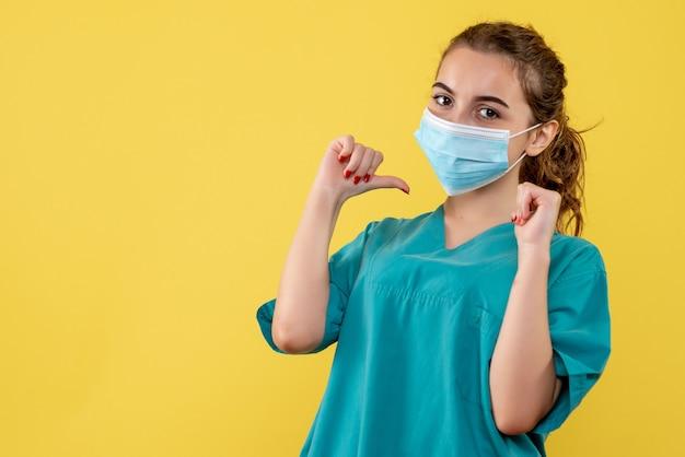 Vorderansicht ärztin in medizinischem hemd und maske, viruspandemiegesundheitsfarbe covid-19 coronavirus