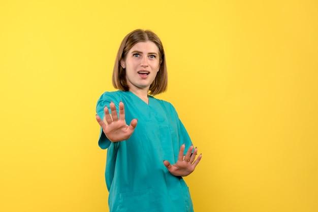 Vorderansicht ärztin mit unzufriedenem ausdruck auf gelbem raum
