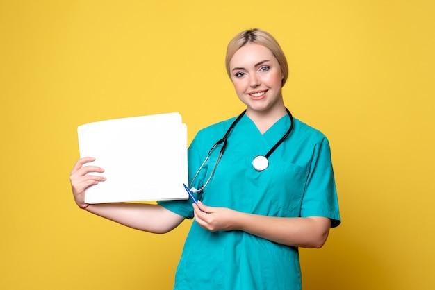 Vorderansicht ärztin mit verschiedenen papieren, virus pandemie gesundheitsmediziner covid-19 krankenschwester