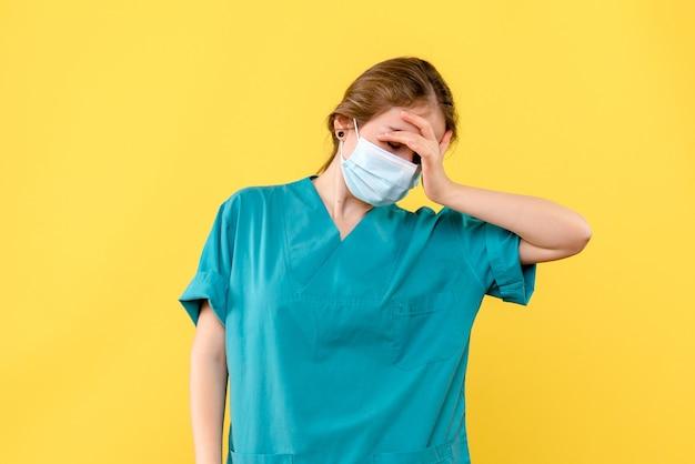 Vorderansicht ärztin müde von der arbeit an gelbem hintergrund krankenhausgesundheit covidpandemie