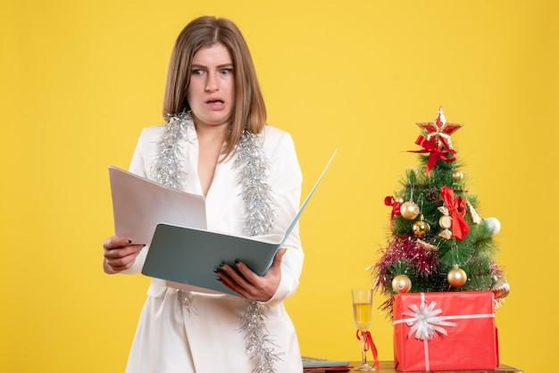 Vorderansicht-ärztin stehend und hält dokumente auf gelbem hintergrund mit weihnachtsbaum und geschenkboxen