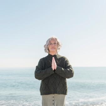 Vorderansicht alte frau, die am strand meditiert