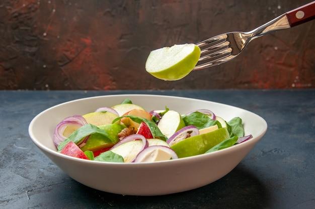 Vorderansicht apfelsalat in schüssel apfel auf gabel auf dunklem isoliertem tisch